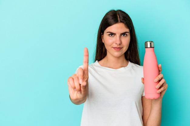指でナンバーワンを示す青い背景で隔離の水筒を保持している若い白人女性。