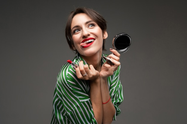 A young caucasian woman holds makeup brushes isolated on grey background