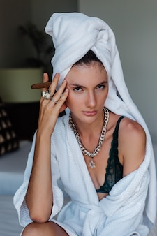 Young caucasian woman in hotel room in bathrobe and white towel on had with cigar.