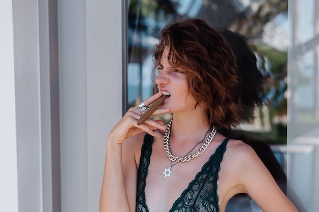 Giovane donna caucasica nella camera d'albergo in biancheria intima con il sigaro.