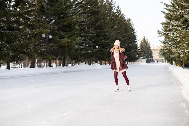 雪に覆われた冬の公園で若い白人女性アイススケート