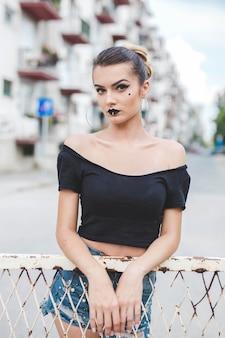 검은 자르기 상단과 찢어진 청바지 반바지를 입은 젊은 백인 여성이 정면을 바라보고 있습니다.