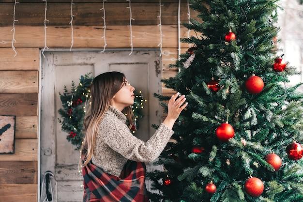 격자 무늬의 젊은 백인 여자는 목조 주택 베란다에 크리스마스 트리를 장식합니다.