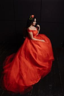 黒のヴィンテージの赤いドレスを着た若い白人女性。