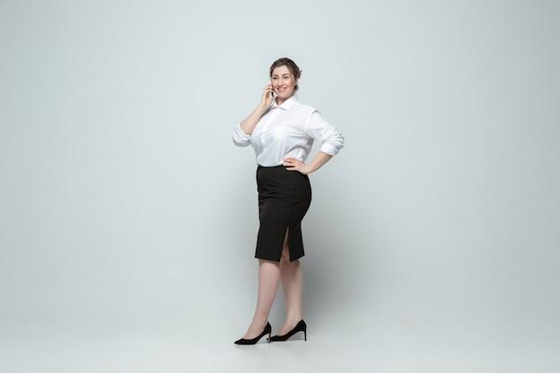 灰色のカジュアルな服装で若い白人女性。ボディポジティブな女性キャラクター、プラスサイズ