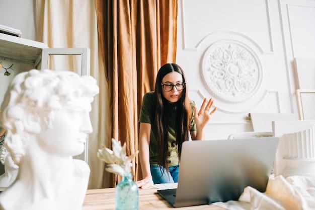 Молодая кавказская женщина в очках работает на портативном компьютере в домашней художественной студии с помощью видеозвонка.