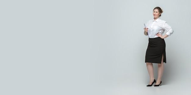 灰色の表面のボディポジティブな女性のキャラクターとサイズのオフィスの服装の若い白人女性