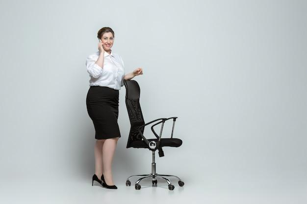 회색 벽에 사무실 복장에 젊은 백인 여자