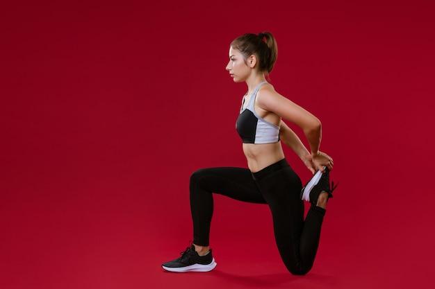 Молодая кавказская женщина в спортивной черной одежде тренируется фитнесом на красной стене концепции здорового образа жизни
