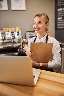 Молодая кавказская женщина в униформе в кафе-баре