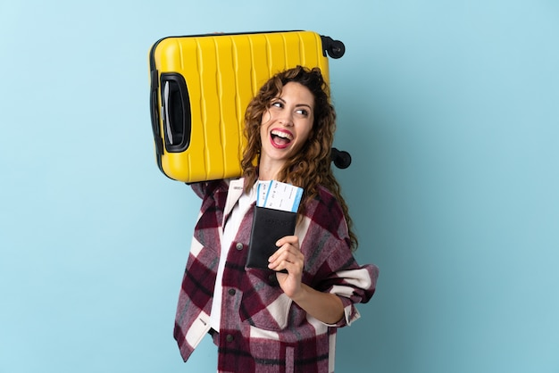 Молодая кавказская женщина в отпуске с чемоданом и паспортом