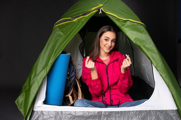 お金のジェスチャーを作るキャンプの緑のテントの中の若い白人女性