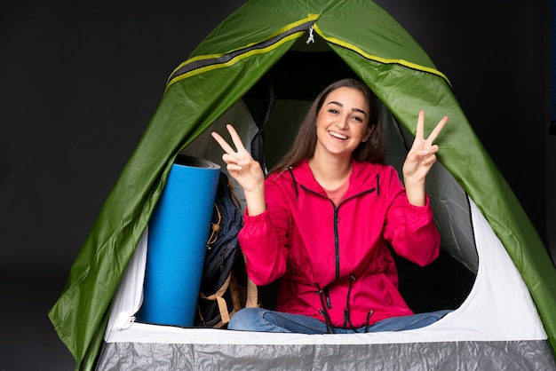 両手で勝利のサインを示すキャンプの緑のテントの中の若い白人女性