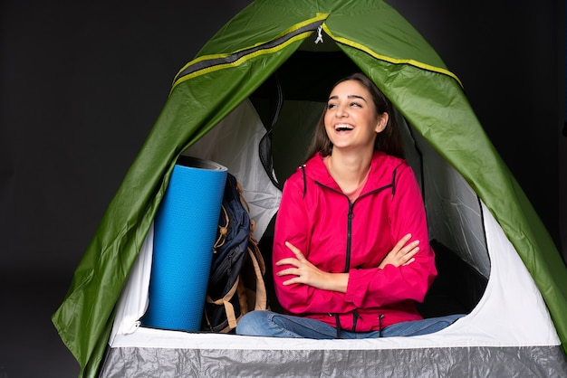Young caucasian woman inside a camping green tent