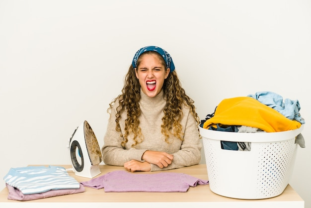Young caucasian woman ironing clothes isolated screaming very angry and aggressive.