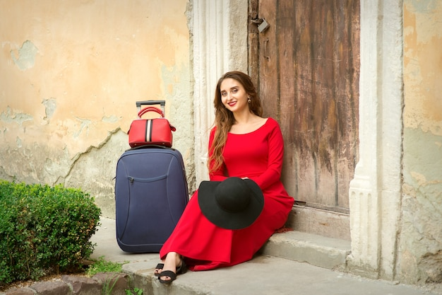 A young caucasian woman is sitting on the threshold of an old house in a red long dress with suitcase outdoors
