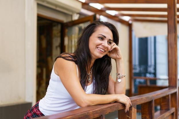 若い白人女性がカジュアルな服を着て店のドアの近くのポーチに立って笑っているきれいな女性...