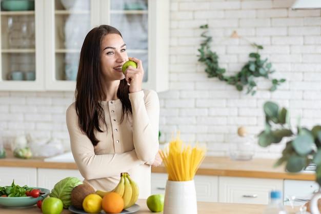 若い白人女性は、彼女の手に青リンゴを持って台所に立っています。健康的なライフスタイルと健康的な食品の概念