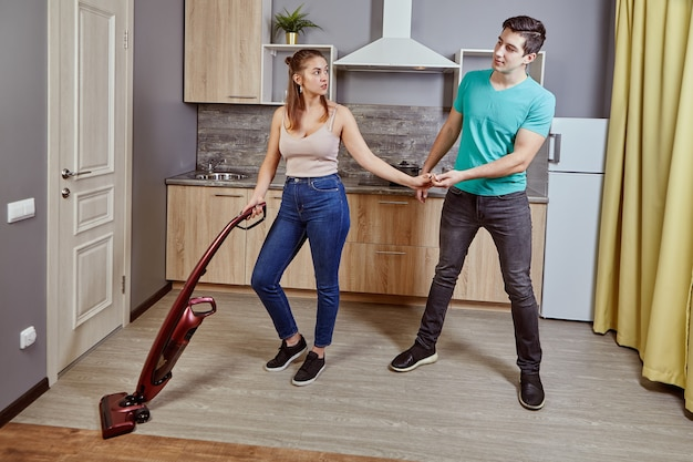 Young caucasian woman is tidying up kitchen using cordless vacuum cleaner, white man took her hand, preventing her from working. it sexual harassment in workplace.