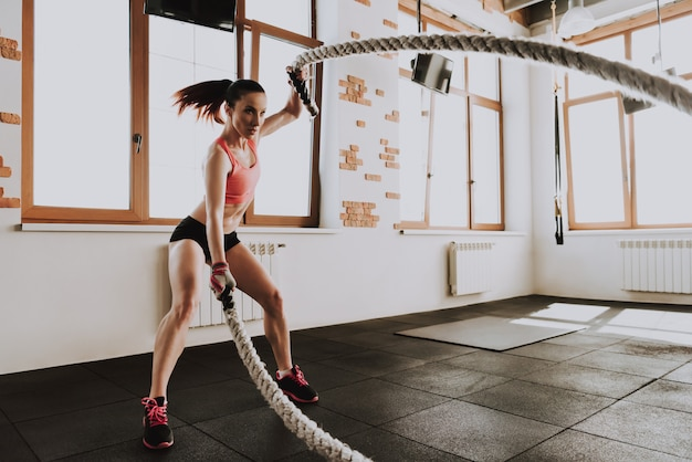 Young caucasian woman is training with ropes