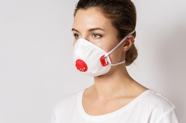 Молодая кавказская женщина носит маску для защиты от вируса