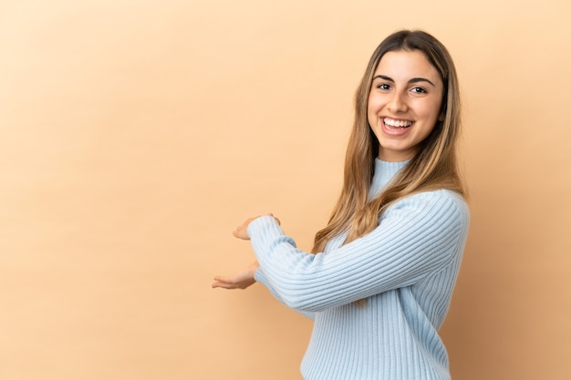 Young caucasian woman isolated on beige background extending hands