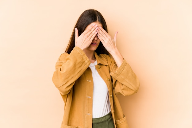 Young caucasian woman isolated on beige wall afraid covering eyes with hands.