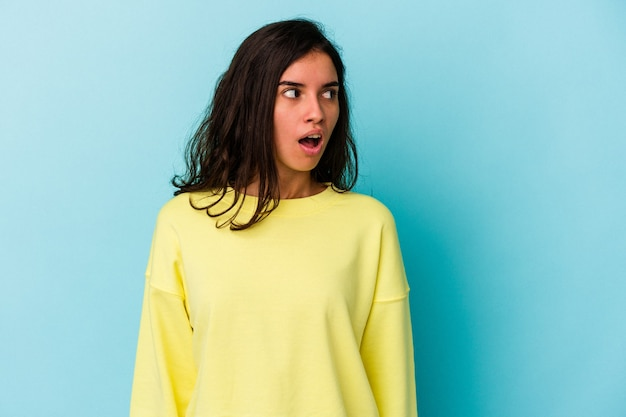 Young caucasian woman isolated on blue background being shocked because of something she has seen.