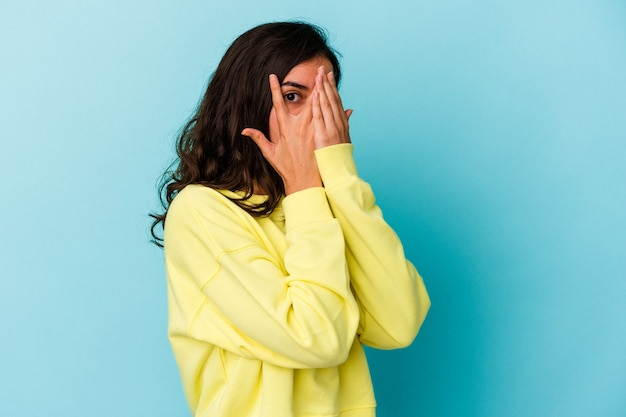 Young caucasian woman isolated on blue background blink through fingers frightened and nervous.