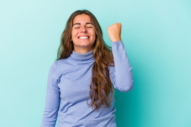 Young caucasian woman isolated on blue background  celebrating a victory, passion and enthusiasm, happy expression.