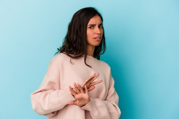 Young caucasian woman isolated on blue background doing a denial gesture