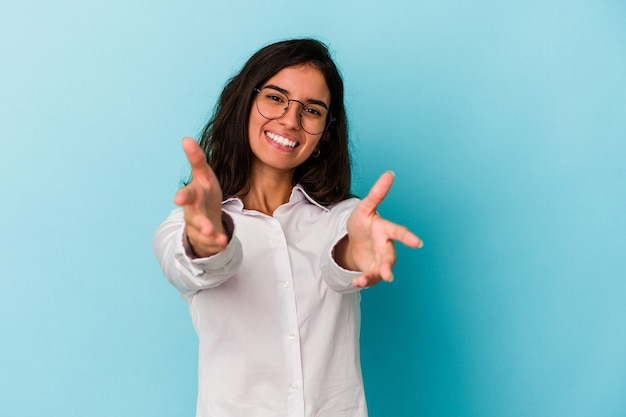 Young caucasian woman isolated on blue background feels confident giving a hug to the camera.