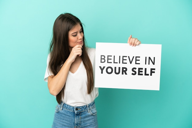 Young caucasian woman isolated on blue background holding a placard with text believe in your self and thinking