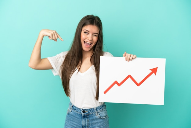 Young caucasian woman isolated on blue background holding a sign with a growing statistics arrow symbol and doing strong gesture