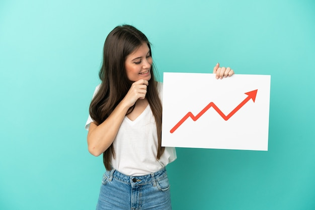 Young caucasian woman isolated on blue background holding a sign with a growing statistics arrow symbol and thinking