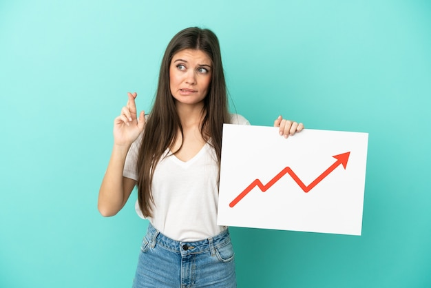 Young caucasian woman isolated on blue background holding a sign with a growing statistics arrow symbol with fingers crossing