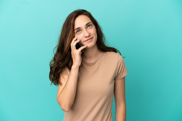 Young caucasian woman isolated on blue background keeping a conversation with the mobile phone with someone