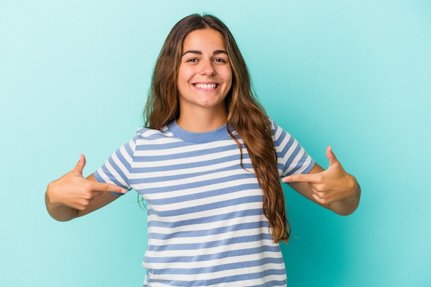 Young caucasian woman isolated on blue background  points down with fingers, positive feeling.
