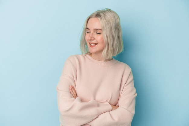 Young caucasian woman isolated on blue background smiling confident with crossed arms.