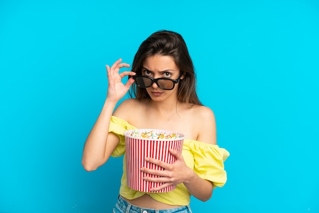 Young caucasian woman isolated on blue background surprised with 3d glasses and holding a big bucket of popcorns