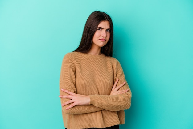 Young caucasian woman isolated on blue background suspicious, uncertain, examining you.