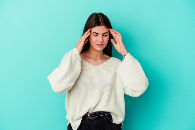 Young caucasian woman isolated on blue background touching temples and having headache.