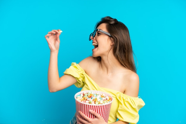 Young caucasian woman isolated on blue background with 3d glasses and holding a big bucket of popcorns