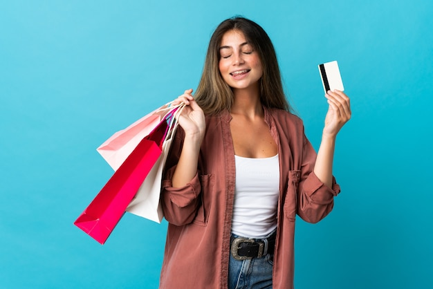Young caucasian woman isolated on blue holding shopping bags and a credit card