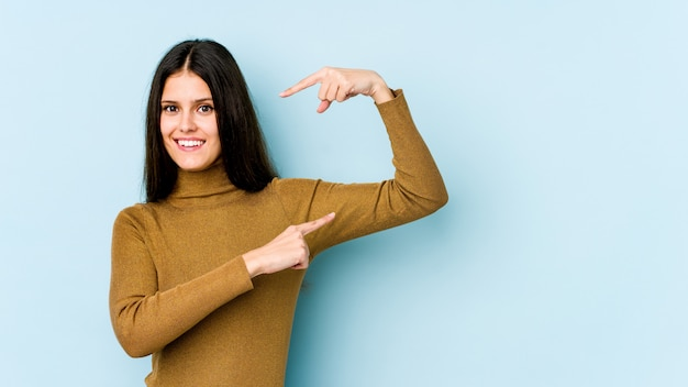 Young caucasian woman isolated on blue wall holding something little with forefingers, smiling and confident.