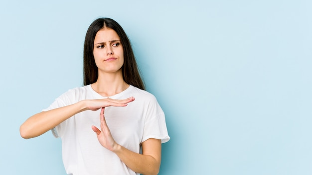 Young caucasian woman isolated on blue wall showing a timeout gesture.