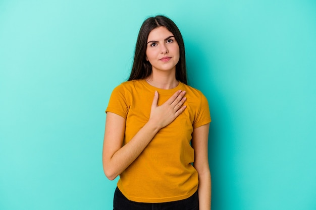 Young caucasian woman isolated on blue wall taking an oath, putting hand on chest.