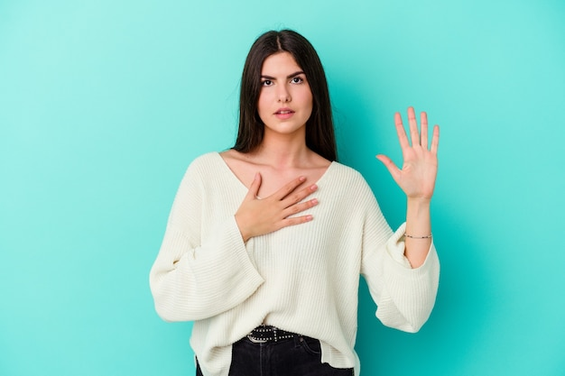 Young caucasian woman isolated on blue wall taking an oath, putting hand on chest