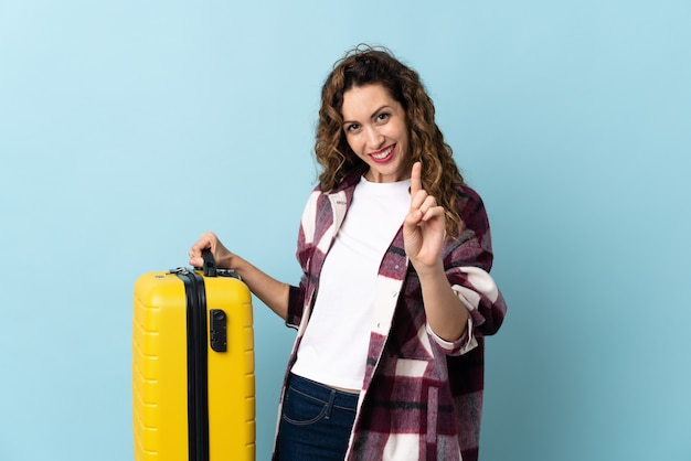 Young caucasian woman isolated on blue wall in vacation with travel suitcase and counting one