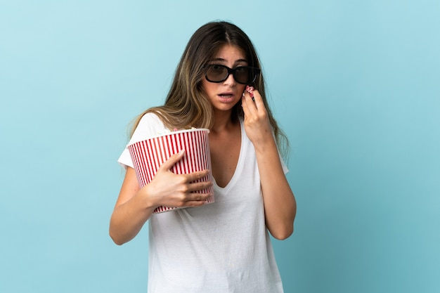 Young caucasian woman isolated on blue with 3d glasses and holding a big bucket of popcorns